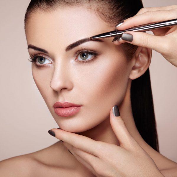beautiful-brunette-woman-paints-the-eyebrows-PPV9FSP-min