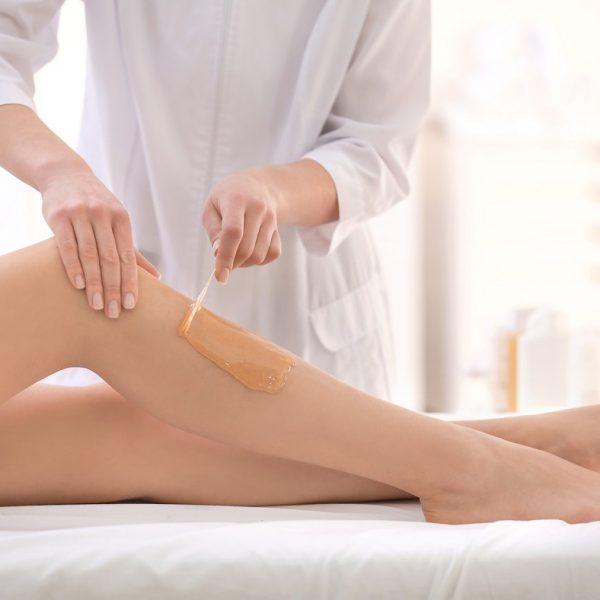 Beautician waxing female legs in spa center